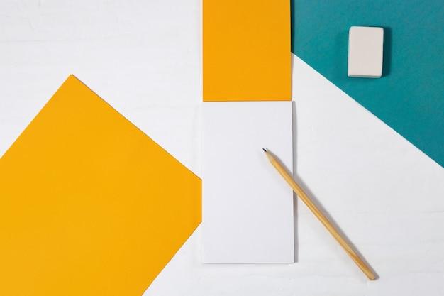 Blocco da disegno giallo brillante, matita di legno, gomma sul tavolo. oggetti per disegnare su un desktop leggero. vista dall'alto con spazio di copia. disteso.
