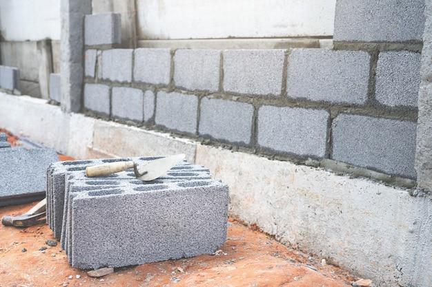 Blocco di cemento e spatola a spatola in cantiere.