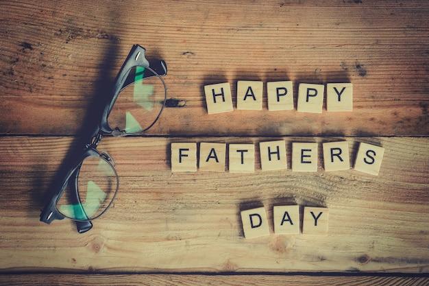 Blocco di giorno felice del padre con gli occhiali su priorità bassa di legno.