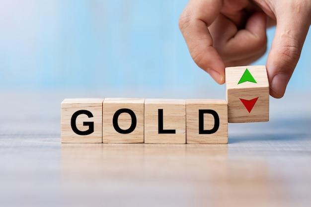 Blocco di legno del cubo del cambiamento della mano dell'uomo di affari con il testo dell'oro al simbolo su e giù della freccia