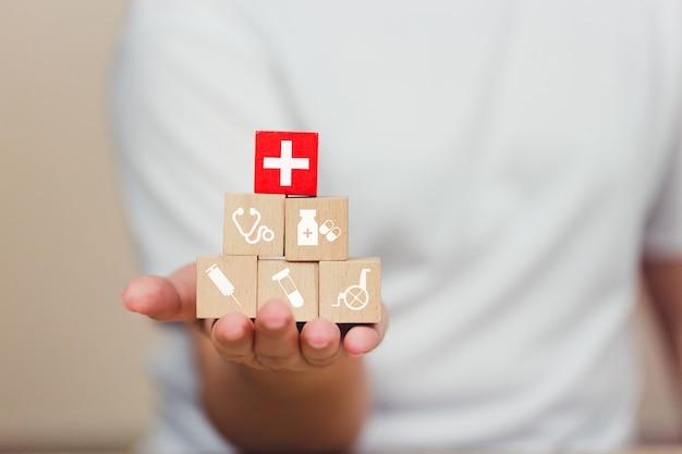 Blocco di legno dell'assicurazione malattia che impila con l'assistenza sanitaria dell'icona medica.