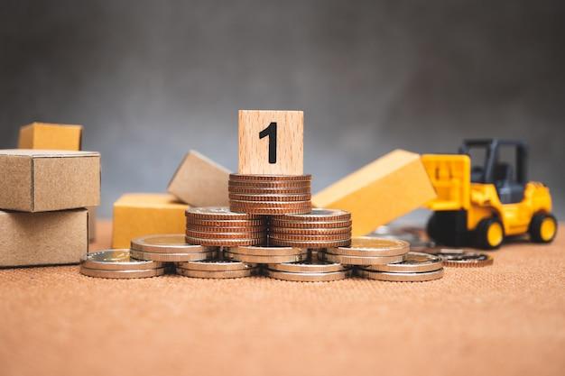 Blocco di legno numero uno sul mucchio di monete con scatole di cartone e veicolo carrello elevatore