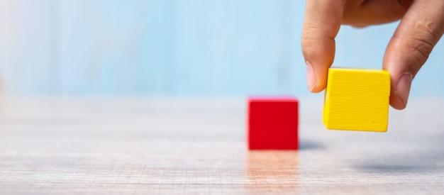 Blocco di legno sull'edificio. pianificazione aziendale, gestione dei rischi, soluzione, strategia, diversa e unica