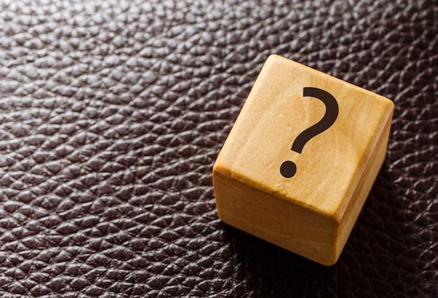 Blocco giocattolo in legno con punto interrogativo in pelle