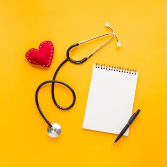 Blocco note a spirale bianco con penna; a forma di cuore cucito; stetoscopio sopra sfondo giallo brillante