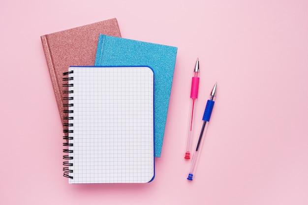 Blocco note a spirale con penne come modello per il tuo design sul rosa. torna al concetto di scuola. copia spazio, vista dall'alto.