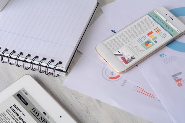 Blocco note a spirale, documenti finanziari e smartphone con statistiche sulla crescita dell'azienda