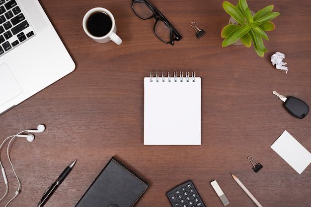 Blocco note a spirale in bianco circondato con forniture per ufficio; gadget; tazza di tè e pianta su un tavolo di legno