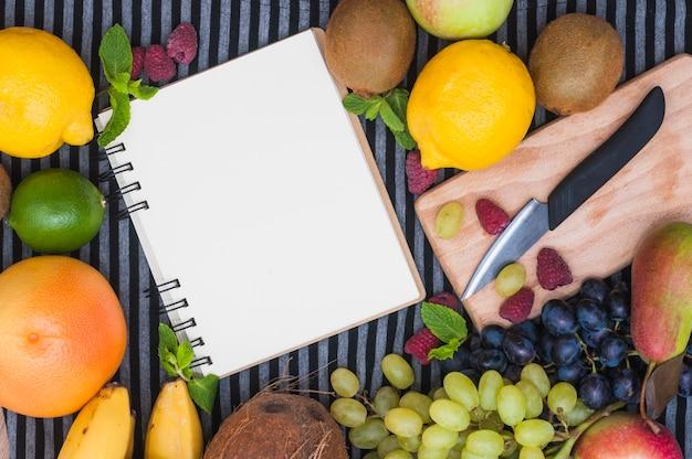Blocco note a spirale in bianco circondato con frutta colorata e coltello sul tagliere