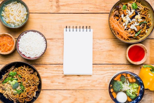 Blocco note a spirale in bianco con cibo tradizionale tailandese sopra la tavola di legno