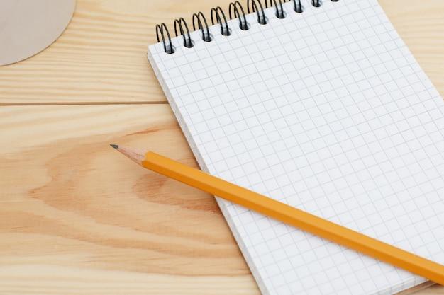 Blocco note a spirale in bianco con la matita che mette su scrittorio di legno. tavolo scrivania design moderno con pagina di blocco note vuota
