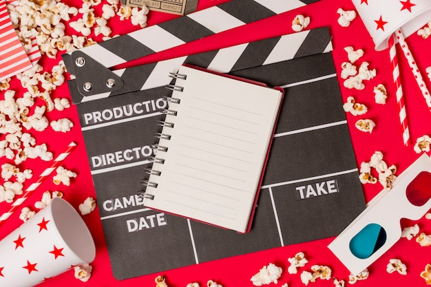 Blocco note a spirale su ciak con vetro monouso; popcorn; bere cannuccia e occhiali 3d su sfondo rosso