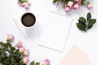 Blocco note a spirale; tè nero; penna e fiori su sfondo bianco