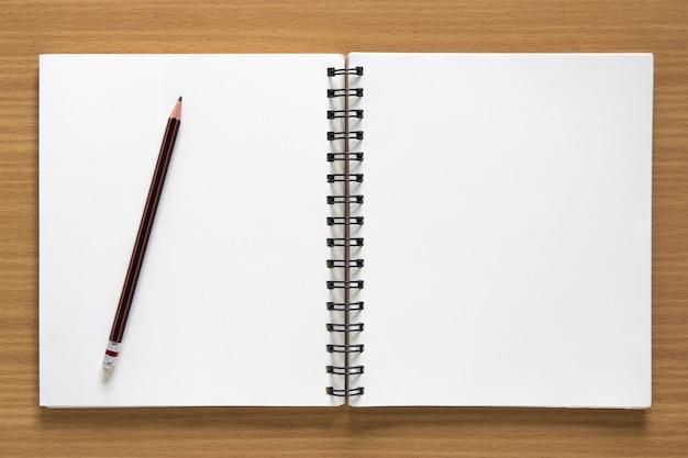 Blocco note a spirale vuota e matita su sfondo di legno