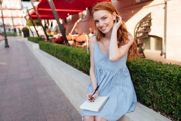 Blocco note adorabile della tenuta della ragazza della testarossa e una penna