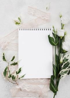 Blocco note bianco di vista superiore con i fiori sul tavolo