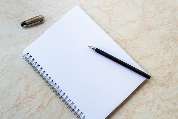 Blocco note bianco vuoto con la penna nera.
