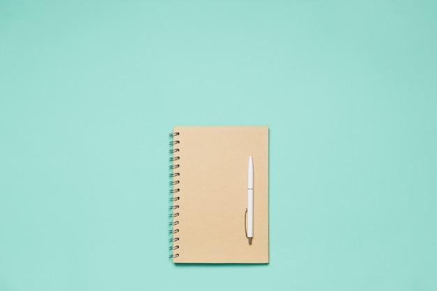 Blocco note composizione piatta con penna sullo scrittorio della menta