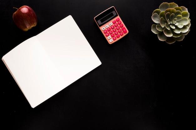 Blocco note con calcolatrice sulla scrivania nera