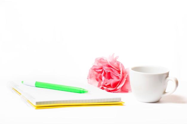 Blocco note con fiori rossi e una tazza su uno sfondo bianco