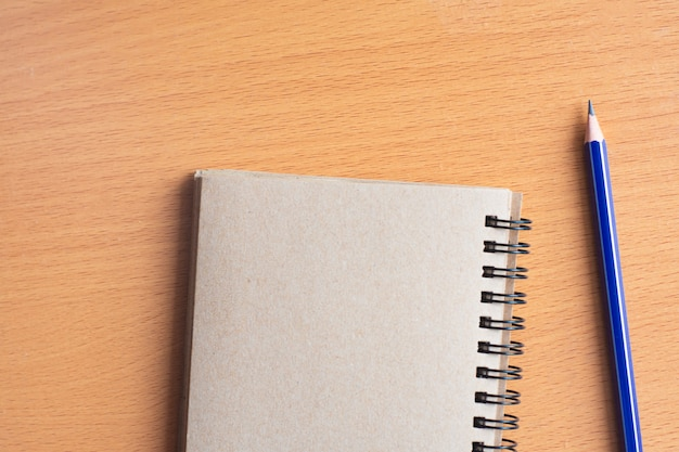 Blocco note con la matita sul fondo del bordo di legno facendo uso della carta da parati per istruzione, foto di affari. prenda nota del prodotto per il libro con lo spazio della carta e di concetto, dell'oggetto o della copia.
