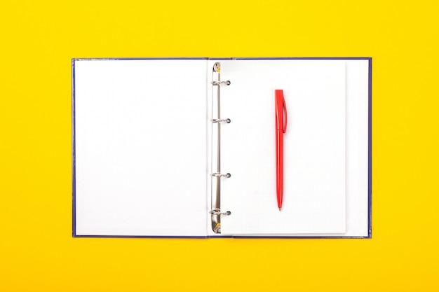 Blocco note con la penna a sfera isolata su fondo giallo