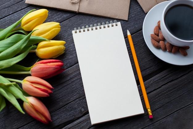 Blocco note con matita accanto a tulipani, caffè e buste.