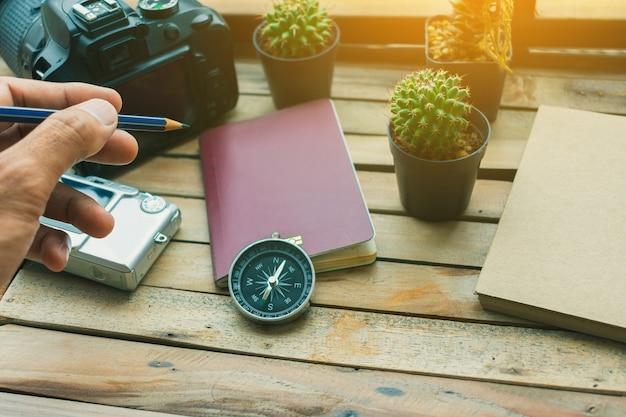 Blocco note con passaporto, macchina fotografica e smartphone su legno