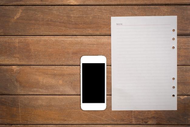 Blocco note con telefono astuto sul tavolo di legno dell'ufficio.