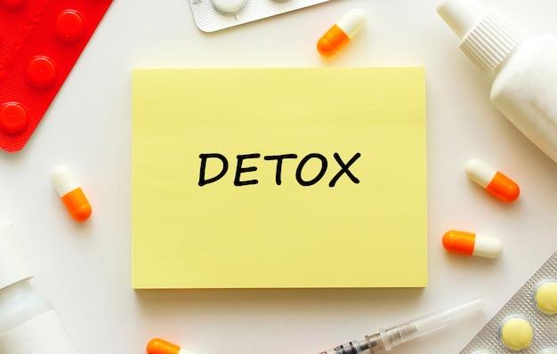 Blocco note con testo detox accanto a pillole e capsule