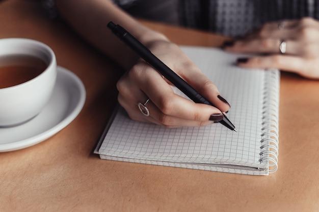 Blocco note di scrittura della mano della donna sulla tavola di legno in caffetteria