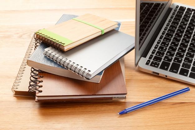 Blocco note e computer portatile sulla tavola di legno