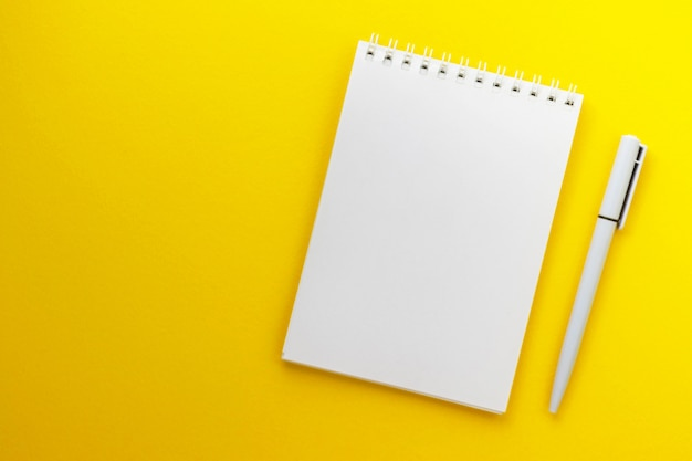 Blocco note e penna in bianco su fondo giallo scuro d'avanguardia