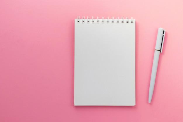 Blocco note e penna in bianco su sfondo rosa scuro alla moda.