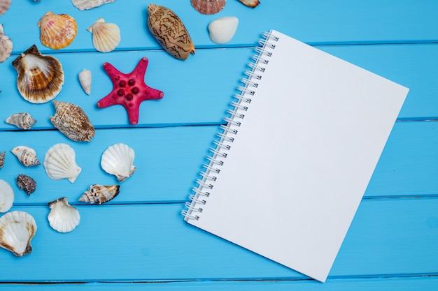 Blocco note e stella di mare e coperture in bianco su fondo blu di legno.
