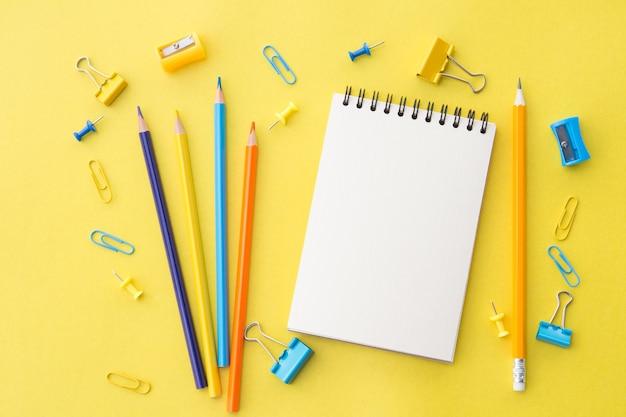 Blocco note in bianco bianco con matite e forniture per ufficio su giallo, piatto laici