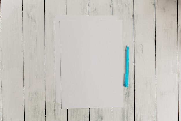 Blocco note in bianco con la penna sulla tavola di legno dell'ufficio.
