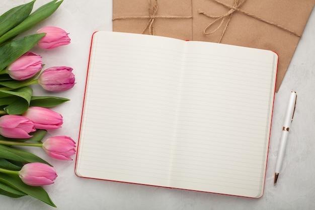 Blocco note in bianco con penna e tulipani.
