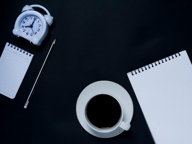 Blocco note, matita, sveglia e caffè nero
