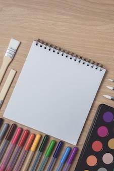 Blocco note o quaderno con molte penne colorate