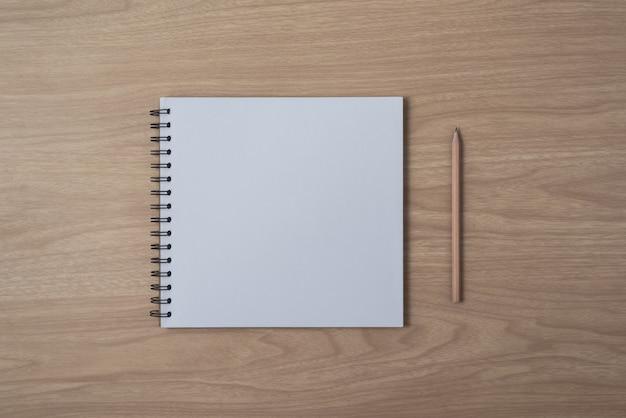 Blocco note o taccuino con la matita sulla tavola di legno marrone