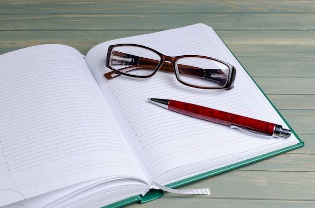 Blocco note, occhiali, penna stilografica su legno