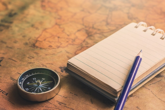 Blocco note per la nota con la matita, bussola sulla mappa di carta per l'immagine di scoperta di avventura di viaggio