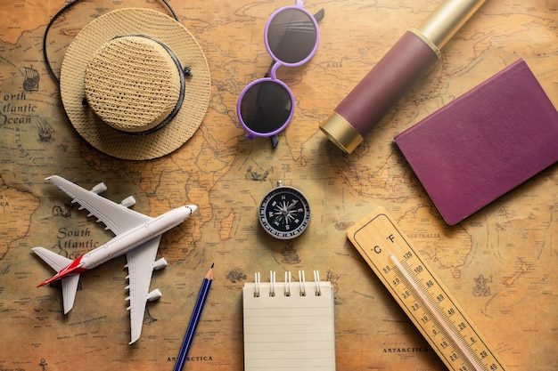 Blocco note per la nota con passaporto, binocolo, matita, bussola, aereo sulla mappa cartacea per l'immagine di scoperta di avventura di viaggio