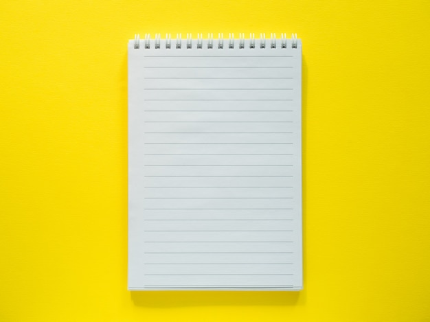 Blocco note per scrivere sul desktop giallo, disteso, copia spazio.