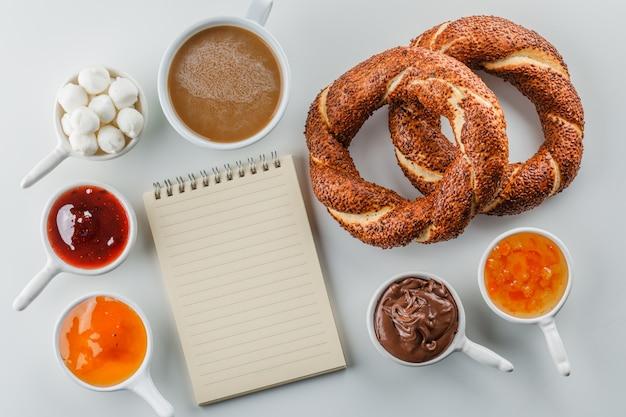 Blocco note piatto e una tazza di caffè con marmellate, lamponi, zucchero, cioccolato in tazze, bagel turco sulla superficie bianca