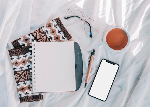 Blocco note, smartphone e tazza sul panno del letto