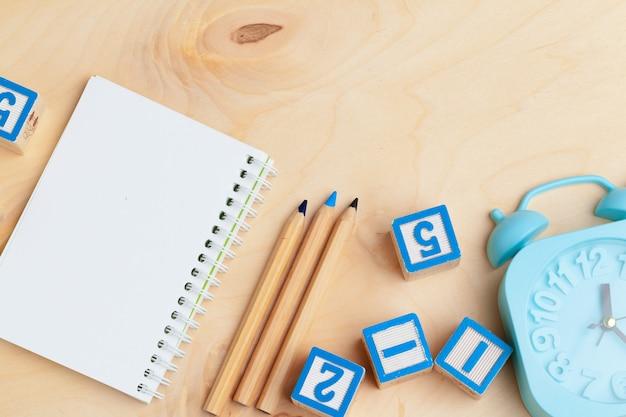 Blocco note sulla tavola di legno e sui blocchetti di alfabeto di legno