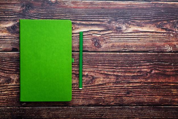 Blocco note verde con un pennarello su una tavola di legno marrone, vista superiore.