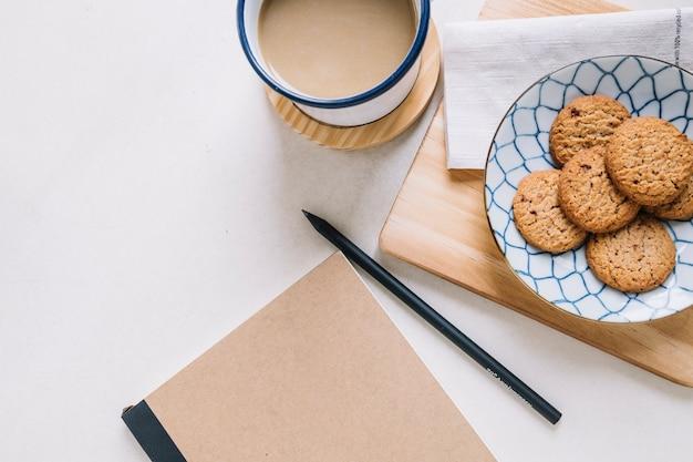 Blocco note vicino a biscotti e caffè